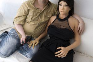 Dirk und Jenny sitzen auf dem Sofa und schauen fernsehen.