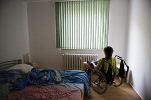 Jenny sitzt im Rollstuhl vor dem Fenster. Sie wiegt Ÿber 50kg, deshalb schiebt Dirk sie im Rollstuhl durch die Wohnung. Die RŠume sind alle abgedunkelt, damit die Nachbarn nicht reinschauen kšnnen und die Puppe entdecken.